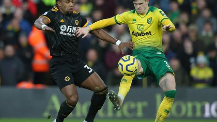 Norwich City defender Sam Byram, right, holds off the challenge of Wolves winger Adama Traore at Car