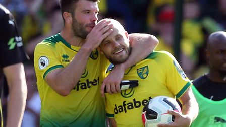 Teemu Pukki gets a hug from Grant Hanley after a Premier League hat-trick against Newcastle in the h