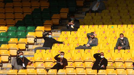Those allowed in shield their eyes form the sun during the Premier League match at Carrow Road, Norw