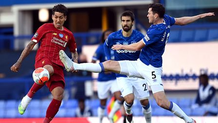 Everton defender Michael Keane, right, challenges Liverpool star Roberto Firmino during Sunday's 0-0