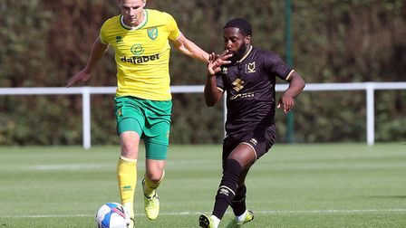 Norwich new boy Jacob Sorensen holds off pressure from David Kasumu of MK Dons