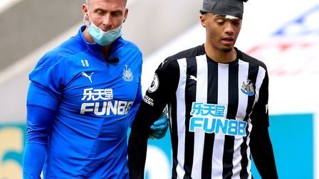 Newcastle United's Jamal Lewis (right) leaves the pitch injured after being fouled by Brighton and H