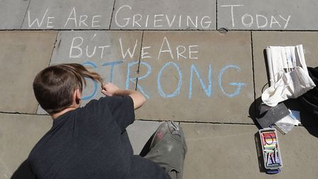 An artist writes a message in St Ann's Square, Manchester, the day after a suicide bomber killed 22