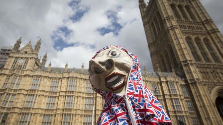 A puppet depicting Prime Minister Theresa May stands in front of the Houses of Parliament in Westmin