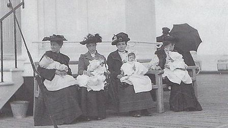 BABY-SITTING 1900-STYLE: women holding their youngsters in front of the old lamp-house at the end of