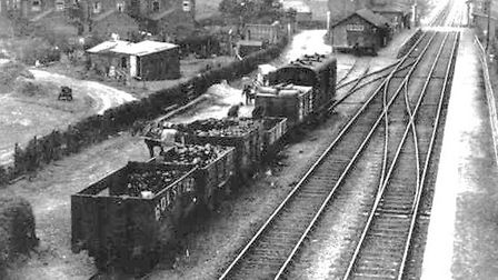 (MAIN PICTURE) WELCOME SIGHT: coal being shovelled from railway trucks on to a horse-drawn flat cart