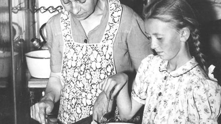 MUMMY'S LITTLE HELPER: schoolgirl Moira Hall sorting out the salad with her mother Alex for Britwell