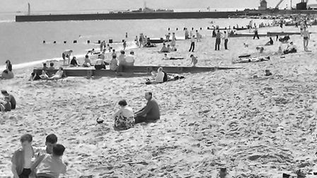 HARBOUR HOLIDAY: beach lovers close to the South Pier in 1954 have a good view of vessels entering a