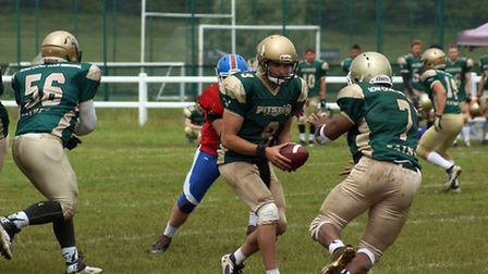 Action from Bury Saints' 26-26 draw at Sussex Thunder - QB (9) Francis Hughes hands ball off to RB (