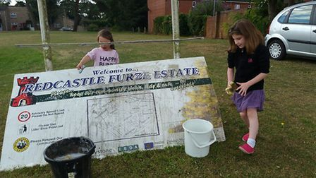 Daisy, left, and Poppy Warnock, right, clean the Redcastle Furze Estate sign in Thetford.