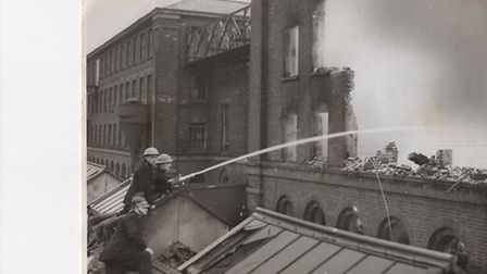 Firemen at work on Grout's mill in Great Yarmouth after wartime bombing in 1941. Its wartime output