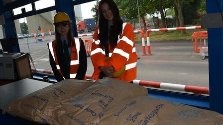 Students take delivery of three sacks of sugar, ingredients for produce they will be making ahead of