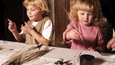 Children having a go at writing with quill pens in the Hall of Ancient House. Picture: Ancient House