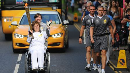 Torchbearer Betty Brown carries the Olympic flame through Filby. Picture: Denise Bradley