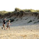 People walking along Caister beach on the east coast of Norfolk. Picture: James Bass
