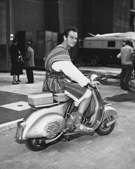 Actor Charlton Heston takes a break from the filming of Ben-Hur by riding a moped to clear his head.