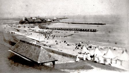 A busy Gorleston beach in a Victorian era summer, with people decorously dressed despite the season.