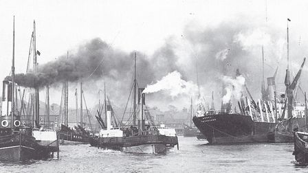 Busy tugs jostle in the River Yare as they help a Scandinavian timber ship into port.