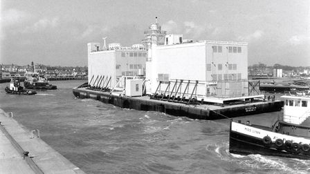 A barge carrying a large prefabricated structure being towed into Yarmouth harbour in 1977.