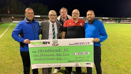 Shrublands FC secretary, John Barrett (right centre) being presented with a cheque by Norfolk Hire a