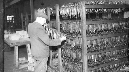 Smoked herring threaded on to speets are placed on racks ready to be packed in 1955.