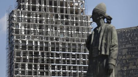 A statue representing the Lebanese expatriate is seen in front of a building that was damaged by an