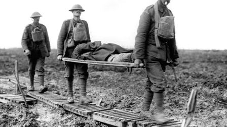 First Battle of Passchendaele. Two guardsmen bringing in a wounded comrade on a stretcher, near Lang