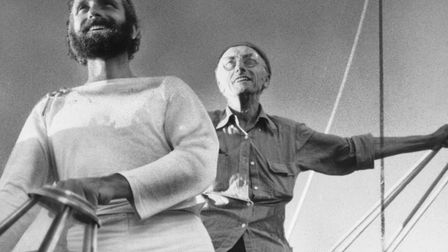 Jacques Cousteau, background, and his son, Phillipe, at the wheel of a ship.