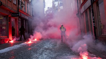 Counter-protesters throw flairs at police as they demonstrate against the neo-nazi Nordic Resistance
