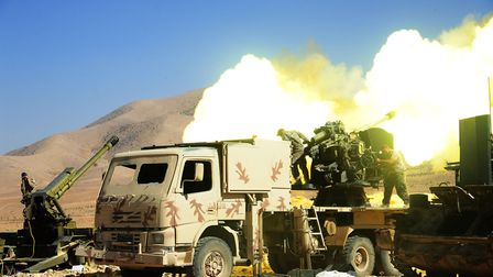 Hezbollah fighters fire at a position of the Islamic State (IS) group in Syria's Qalamoun region. Ph