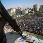 A Hamas gunman watches as Fatah supporters take part in a rally marking the death anniversary of lat