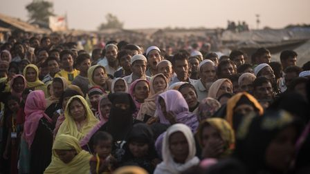 Rohingya Muslim refugees wait to be called to recieve food aid of rice, water, and cooking oil in a