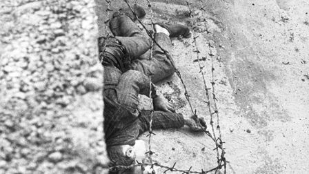 East Berliner Peter Fechter, 18, lies dying on the Eastern side of the Wall after he was shot by bor