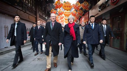 Prime Minister Theresa May and her husband Philip walk through a market after visiting the Yu Yuan T