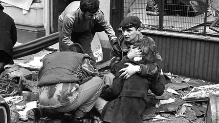 A British paratrooper takes a young girl in his arms to comfort her after she had been hurt in the b