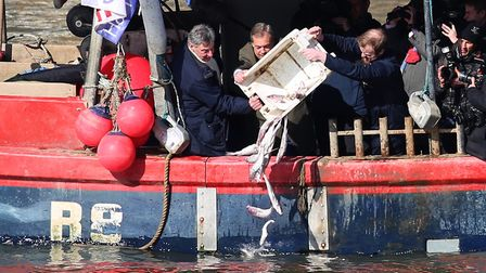 Nigel Farage, centre, and Fishing for Leave founder Aaron Brown, right, throw fish into the river Th