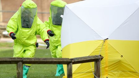 Personnel in hazmat suits work to secure a tent covering a bench in the Maltings shopping centre in