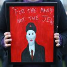 """A demonstrator holding a painting saying""""For the many not the Jew"""" as people protest against anti-Se"""