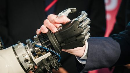 A hand shakes the hand of a robot during at a trade fair in Germany Photo: Ole Spata/dpa