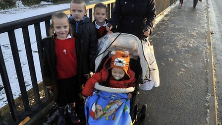 Lisa Robb and her children on the Derby Road bridge that has been slippery for children walking to R