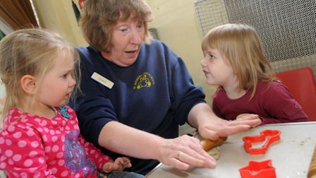 Margaret Davey helps two girls with their play dough at St. Andrew's Pre-School in Felixstowe, which