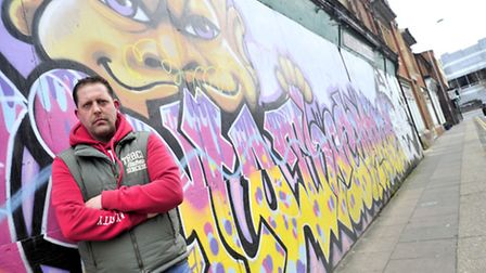 Graffiti artist Scott King with the work that he was commissoned by the council to do in Upper Orwel