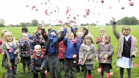Pupils from Ringshall Primary throws their poppies at the Wattisham Airfield