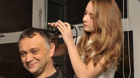 Bethany Leach shaving her dad, Kevin's hair, to raise money for the cancer ward that her father is b