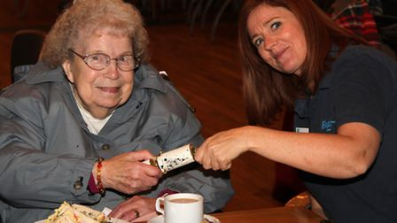 Peggy Brett pulls a cracker with Sally Elliss at the tea St Lawrence Centre in Ipswich after christm