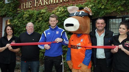 Ipswich Town Football Club's Luke Hyam cuts the ribbon to re-open the Farmhouse at Kesgrave with hel