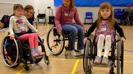 Emily Hatcher (right) and Sister Sophie practice their wheelies with the help of Emily Ellington at