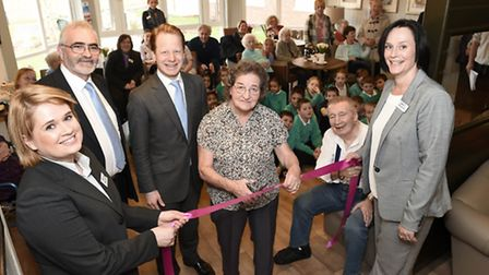 Resident Dot Ridgeway (centre) cuts the ribbon at the new Prince George House care home with (L-R) d