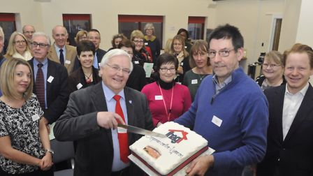 Cllr Roger Fern cuts the cake with Halford Hewitt in the refurbished room named after himself at the