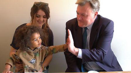 Ed Balls high-fiving 20-month-old Theo Cook who met him with mum Beth.